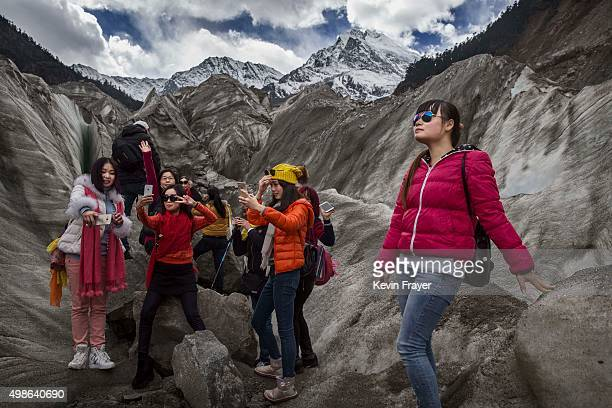 Chinese tourists walk in the tongue of Glacier 1 at the base of the 7556 m Mount Gongga known in Tibetan as Minya Konka on November 13 2015 in...