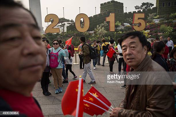 Chinese tourists walk in Tiananmen Square during a polluted morning on October 17 2015 in Beijing China As a result of industry the use of coal and...