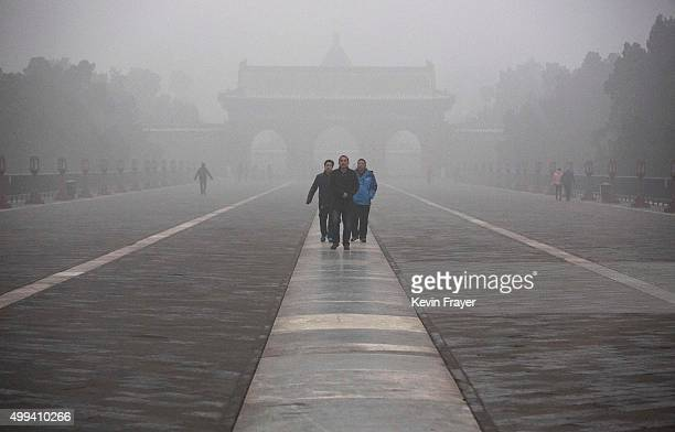 Chinese tourists walk on a hight pollution day in the Temple of Heaven on December 1 2015 in Beijing China China's capital and many cities in the...