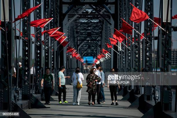 Chinese tourists walk over the 'Friendship Bridge' on the Yalu river in the Chinese border town of Dandong in China's northeast Liaoning province on...