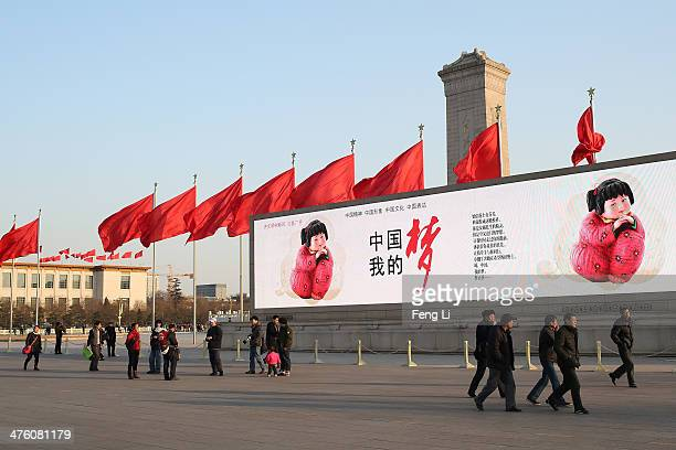 Chinese tourists walk past a LED screen showing the Chinese word 'China Dream' at the Tiananmen Square ahead of the opening of the Chinese People's...