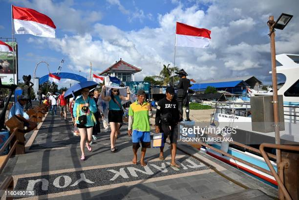 Chinese tourists walk towards their fast boat for a trip to Nusa Penida island from Serangan island in Denpasar, Bali on August 10, 2019.
