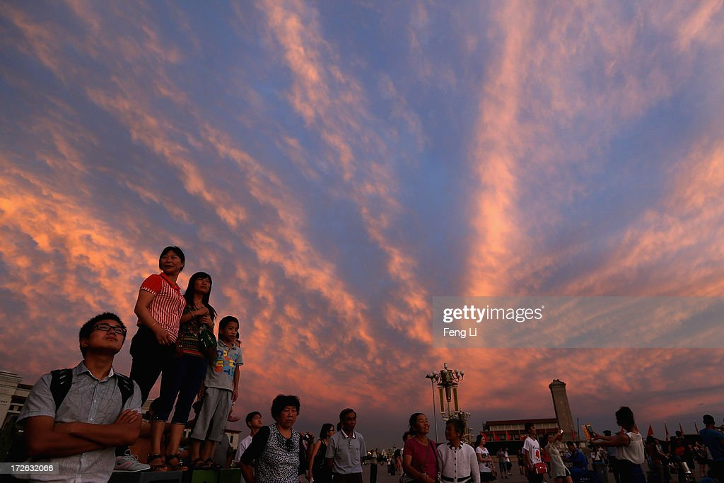 Chinese tourists watch the customary ceremony of lowering flag at Tiananmen Square under crimson clouds at sunset after several days of heavy air pollution on July 4, 2013 in Beijing, China.