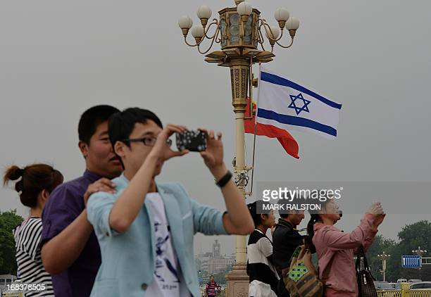 Chinese tourists watch the motorcade of Israeli Prime Minister Benjamin Netanyahu as he arrives to meet the Chinese President Xi Jinping at the Great...