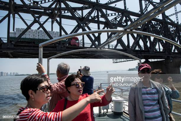 Chinese tourists watch the North Korean border on the Yalu river in the Chinese border town of Dandong, in China's northeast Liaoning province, on...