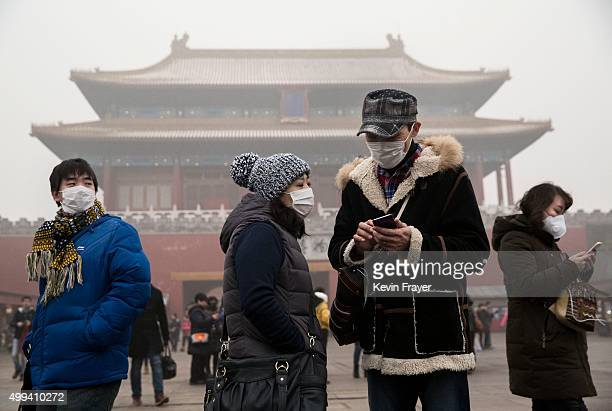 Chinese tourists wear masks as protection from the pollution outside the Forbidden City during a day of high pollution on December 1 2015 in Beijing...