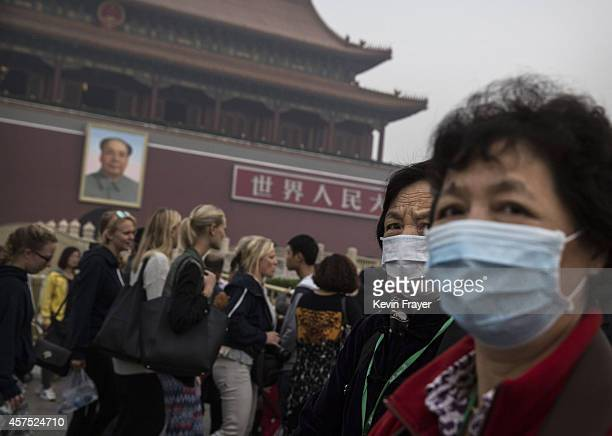 Chinese tourists wear masks during their visit to the Tiannamen Gate near Tiananmen Square October 19 2014 in Beijing China