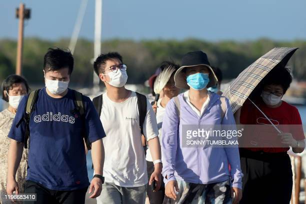 Chinese tourists wearing facemasks as a preventative measure following a coronavirus outbreak which began in the Chinese city of Wuhan, walk after...