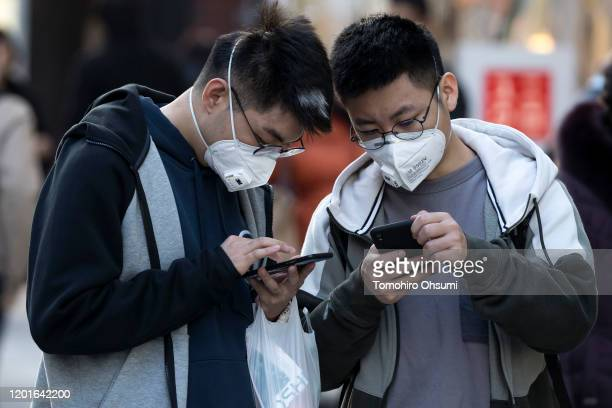 Chinese tourists wearing masks use smartphones in the Ginza shopping district on January 24 2020 in Tokyo Japan While Japan is one of the most...