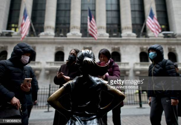 Chinese tourists with facial masks stand in front of the New York Stock Exchange on February 3 2020 at Wall Street in New York City Wall Street...