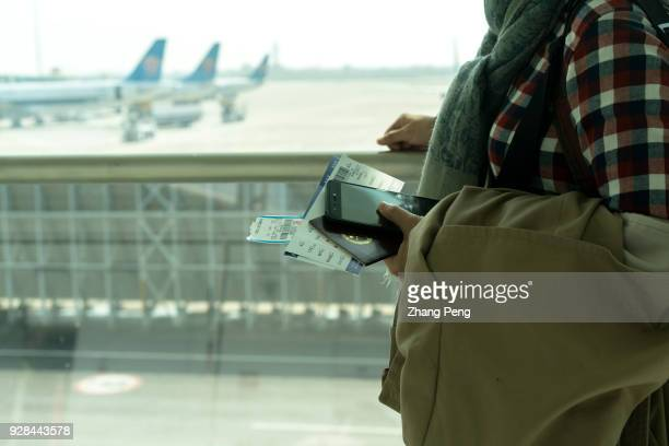 Chinese traveler holding passport and ticket ready to boarding on plane In 2017 the outbound tourists of Chinese nationality broke through 130...