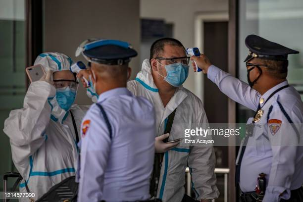 Chinese travelers wearing protective suits have their temperatures checked upon arriving at Ninoy Aquino International Airport after a limited number...
