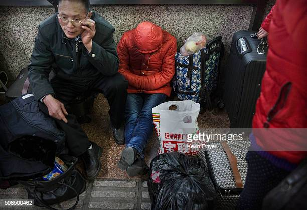 Chinese travellers wait at a railway station on February 4 2016 in Beijing China Millions of Chinese are heading home for the upcoming Chinese New...