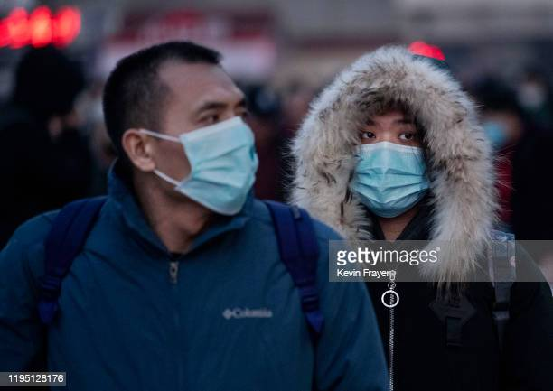 Chinese travellers wear protective masks as they arrive to board trains at Beijing Railway station before the annual Spring Festival on January 21...