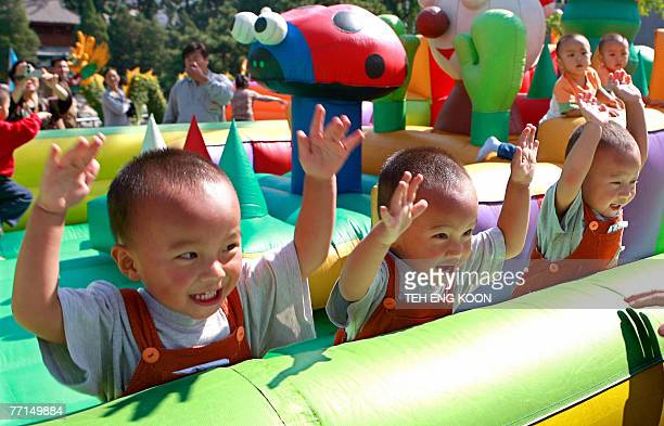 Chinese triplet boys play at a playground during the Beijing Twins Cultural Carnival at a park in Beijing 02 October 2007 Chinese officials have been...