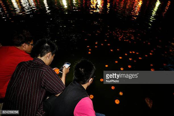 Chinese unmarried men using his mobile phone as he collect mandarin oranges from the lake during Chap Goh Mei festival at a lake in Petaling Jaya...