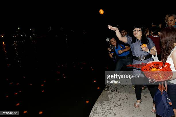 Chinese unmarried women throw mandarin oranges into the lake during Chap Goh Mei festival at a lake in Petaling Jaya near Kuala Lumpur Malaysia 5...