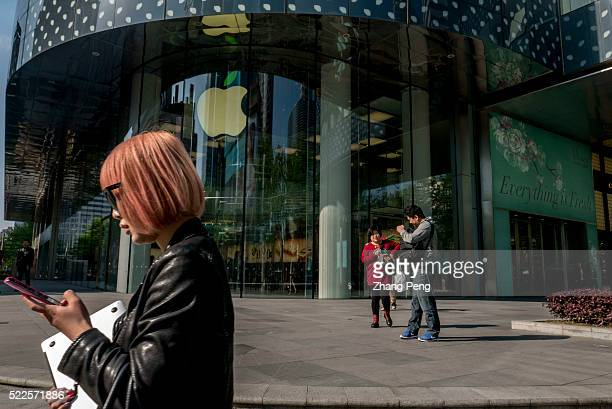 Chinese user holding a Macbook walks past an Apple store on Huaihai road Apple had 28 stores in China through the end of 2015 but it plans to add 12...
