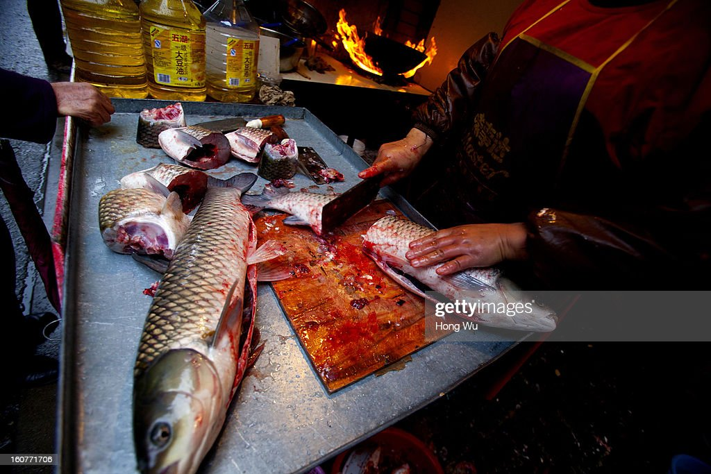 A Chinese vendor chops up a fish for buyers at an outdoor market on February 5, 2013 in Shanghai, China. Chinese citizens are stocking up on food ahead of the upcoming Chinese Lunar New Year, also known as Spring Festival, is one of the most important festivals in China and falls this year on February 10, 2013.