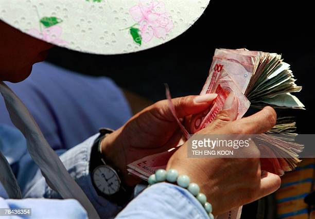 A Chinese vendor counts yuan notes on a street in central Beijing 30 August 2007 China was to sell nearly 80 billion dollars worth of government...