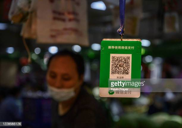 Chinese vendor stands next to a QR code customers scan to pay via the WeChat app at a local market on September 19, 2020 in Beijing, China. The Trump...