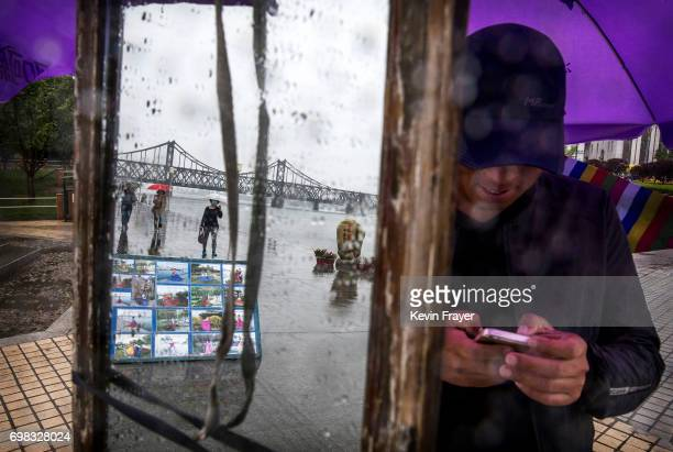 A Chinese vendor waits for customers as the 'Friendship Bridge' that crosses the Yalu river is seen in a mirror in the border city of Dandong...