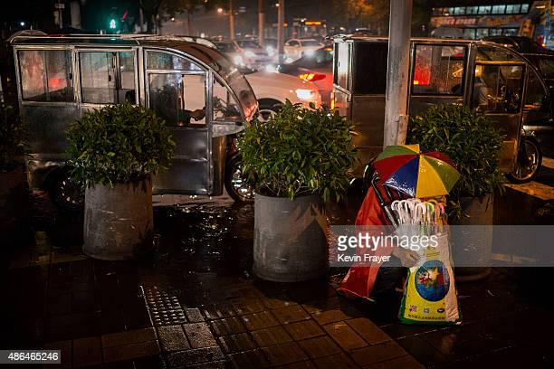 Chinese vendor wears an umbrella hat as he tries to shelter from the rain while selling umbrellas to passersby on a rainy evening on September 4 2014...