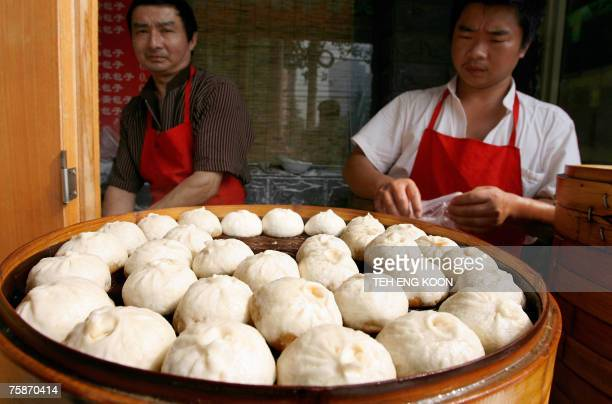 Chinese vendors prepares steaming pork buns on sale at a sidewalk stall in Beijing 25 July 2007 China will soon introduce its first quality standards...