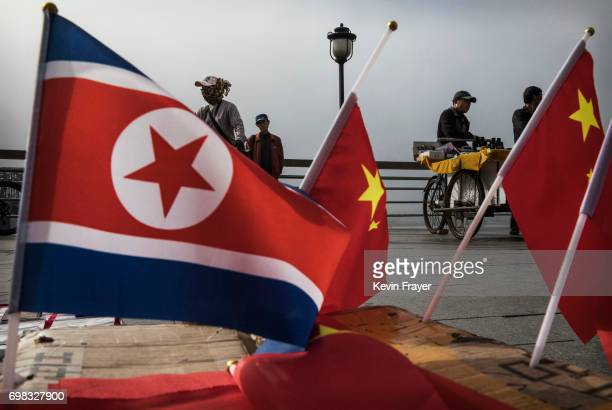 Chinese vendors sell North Korea and China flags on the boardwalk next to the Yalu river in the border city of Dandong Liaoning province northern...