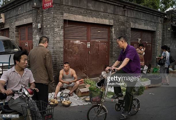 Chinese vendors sell vegetables at a market in a residential neighborhood on May 27 2015 in Beijing China