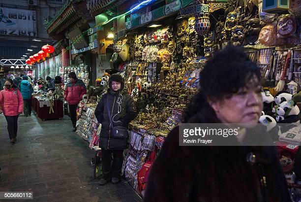 Chinese vendors wait for customers at a market on January 19 2016 in Beijing China In 2015 China's economy grew at its slowest rate in a quarter...