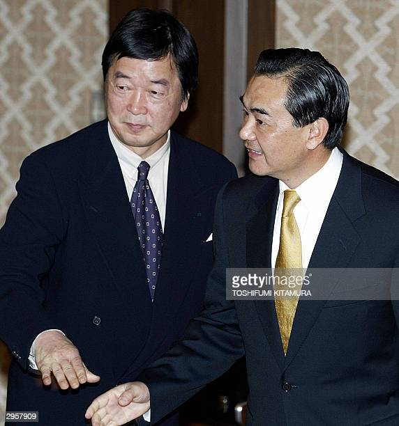 Chinese Vice Foreign Minister Wang Yi walks to his seat after being welcomed by Japanese Deputy Foreign Minister for Political Affairs Hitoshi Tanaka...