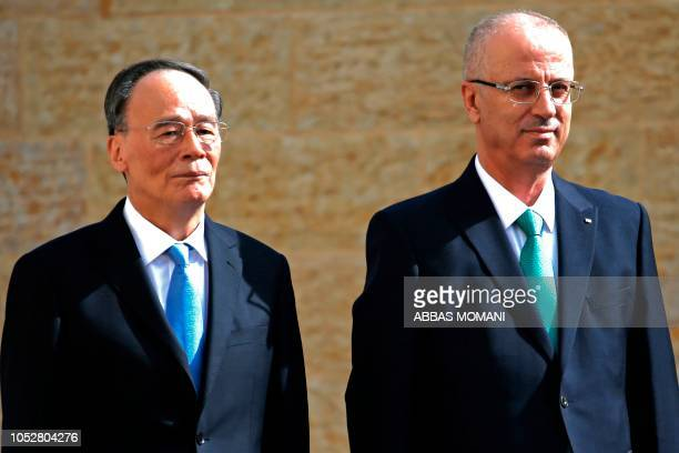 Chinese Vice President Wang Qishan and Palestinian prime minister Rami Hamdallah review the honour guard in the the West Bank city of Ramallah on...