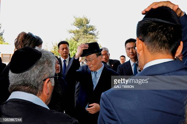Chinese Vice President Wang Qishan covers his head with a hat as he enters a memorial ceremony at the Hall of Remembrance on October 24, 2018 during...