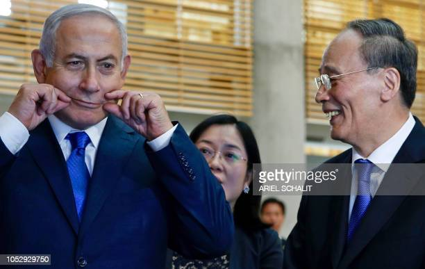 Chinese Vice President Wang Qishan laughs as Israeli Prime Minister Benjamin Netanyahu makes a face during their tour of the Israeli Innovation...