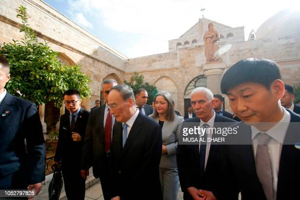 Chinese Vice President Wang Qishan walks with the Palestinian tourism minister Rula Maayah and the Governor of Bethlehem district Kamel Hemeid during...