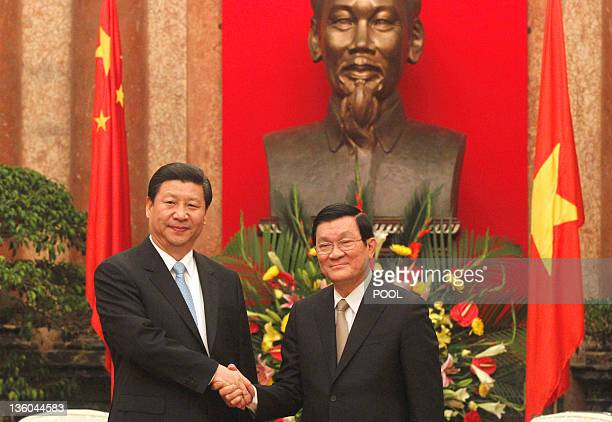 Chinese vice president Xi Jinping shakes hands with Vietnamese president Truong Tan Sang as they meet at the presidential palace in Hanoi on December...