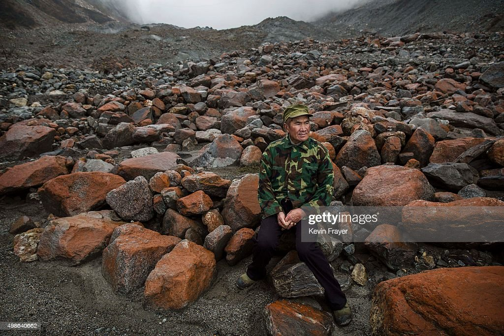 Chinese villager Li Yuanqing, 62, who has witnessed the ice slowly receding, sits near the headwaters of the Glacier River and the end of the tongue of Glacier 1 at the base of the 7,556 m (24,790 ft) Mount Gongga, known in Tibetan as Minya Konka on November 11, 2015 in Hailuogou, Garze Tibetan Autonomous Prefecture, Sichuan province, China. Hailuogou is one of China's 8,500 monsoonal glaciers and the longest of 71 glaciers on the eastern slope of Mt. Gongga. Monsoonal glaciers are found at lower altitudes and are at much higher risk to the effects of rising temperatures and climate change. Chinese scientists studying the impact on the Tibetan plateau warn the ablation rate of monsoonal glaciers is alarming. Data shows the Hailuogou basin glaciers have lost nearly 3 kilometers of mass since the 1960s and the rate is accelerating. Some researchers are concerned the glaciers could shrink at an accelerated rate beyond the present 20 meters a year and thin at a rate of more than 1 meter per year. At an upcoming conference in Paris, the governments of 196 countries will meet to set targets on reducing carbon emissions in an attempt to forge a new global agreement on climate change.