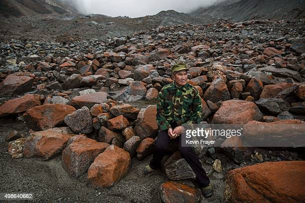 Chinese villager Li Yuanqing who has witnessed the ice slowly receding sits near the headwaters of the Glacier River and the end of the tongue of...