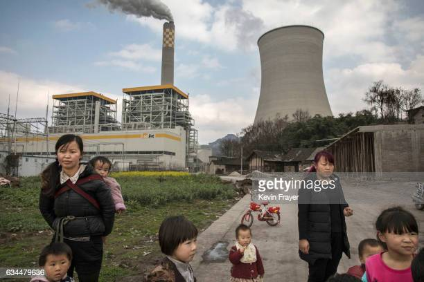 Chinese villagers stand near a newly built stateowned coal fired power plant on February 7 2017 in Liuzhi County Guizhou province southern China A...