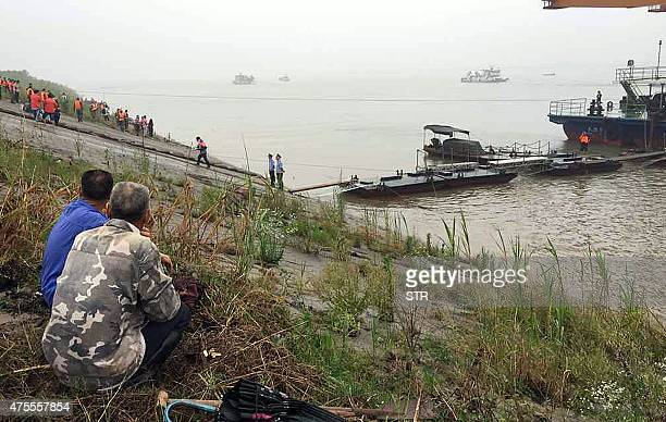 Chinese villagers watch as rescue teams head out to search for survivors of a passenger ship carrying more than 450 people which sunk in the Yangtze...