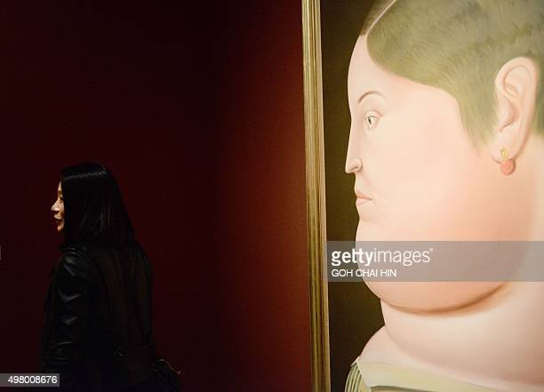 A Chinese visitor admires the works of Colombian artist Fernando Botero at the China National Museum in Beijing on November 20 2015 Botero one of the...