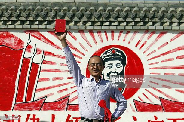 A Chinese visitor proudly holds up a Communist revolutionary Red Book containing the teachings of Mao Zedong as he poses for a picture at a theme...