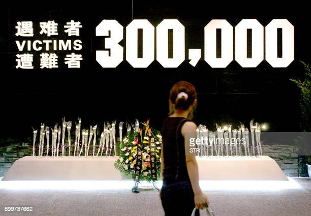 A Chinese visitor walks pass a shrine set up to remember the estimated 300000 victims of the Nanjing massacre at an exhibition in Beijing 23 August...