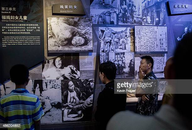 Chinese visitors look at a display showing alleged Japanese atrocities in the Second World War during a visit to the Museum of the War of Chinese...
