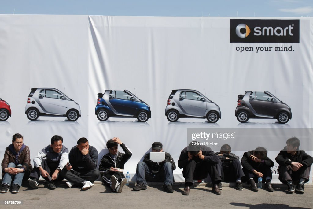 Chinese visitors rest in front of an advertisement billboard at the Beijing Auto Show on April 29, 2010 in Beijing, China. The Beijing auto show has become one of the biggest and most important auto shows in the world as explosive sales growth propelled China.