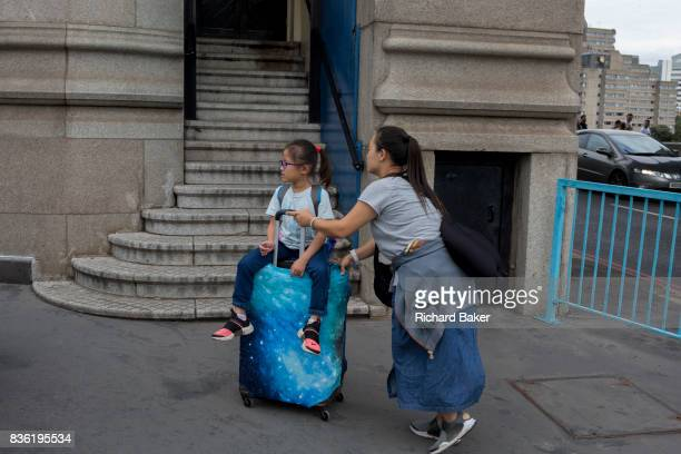 Chinese visitors to London push their baggage with two children riding on top on 14th August 2017 on Tower Bridge in London England