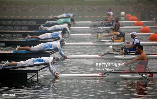 Chinese volunteers hold boats in place before a heat of the men's Single Sculls - A Rowing event at Shunyi Olympic Rowing-Canoeing Park during day...