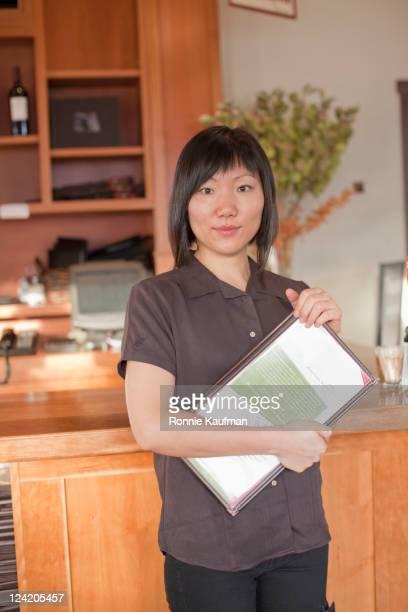 Chinese waitress holding menus in restaurant