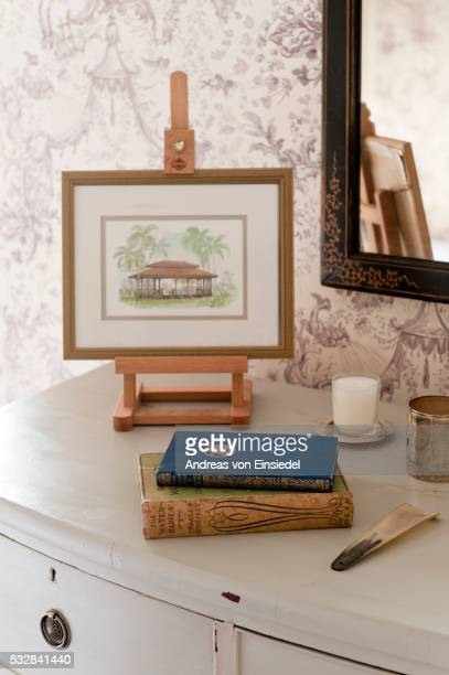 A Chinese watercolour on a miniatue easel on top of a chest of drawers along with a shoe horn and vintage books